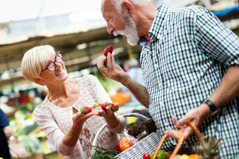 Mature couple shopping vegetables and fruits on the market. Healthy diet. royalty free stock image