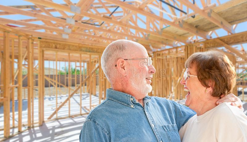 Senior Couple On Site Inside Their New Home Construction Framing royalty free stock photography