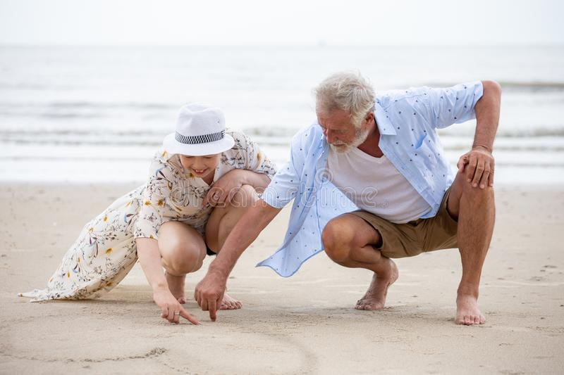 Senior couple sitting on the beach drawing a heart in the sand together ,  woman asian man caucasian. Senior couple sitting on the beach drawing a heart in the stock images