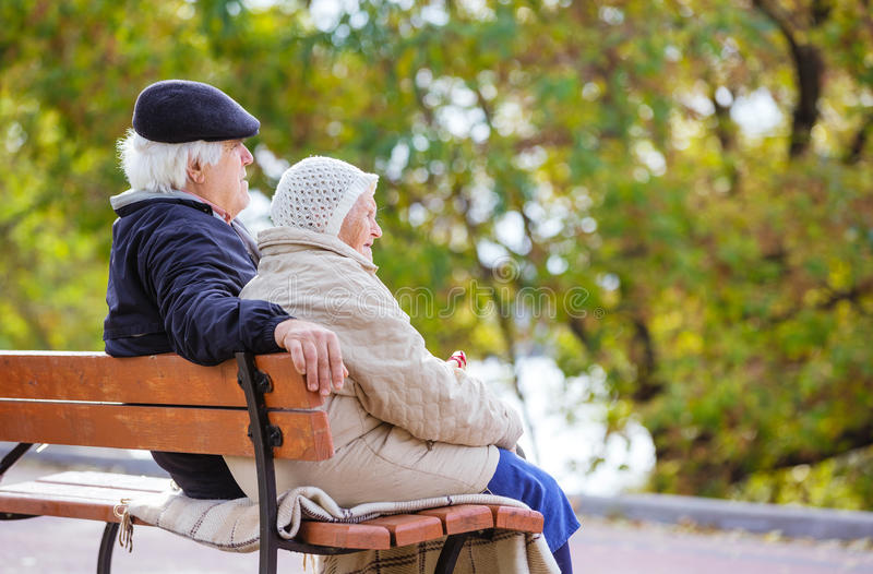 Senior couple sitting on bench in park stock photo