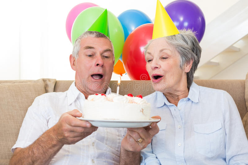 Senior couple sitting on couch celebrating a birthday stock images