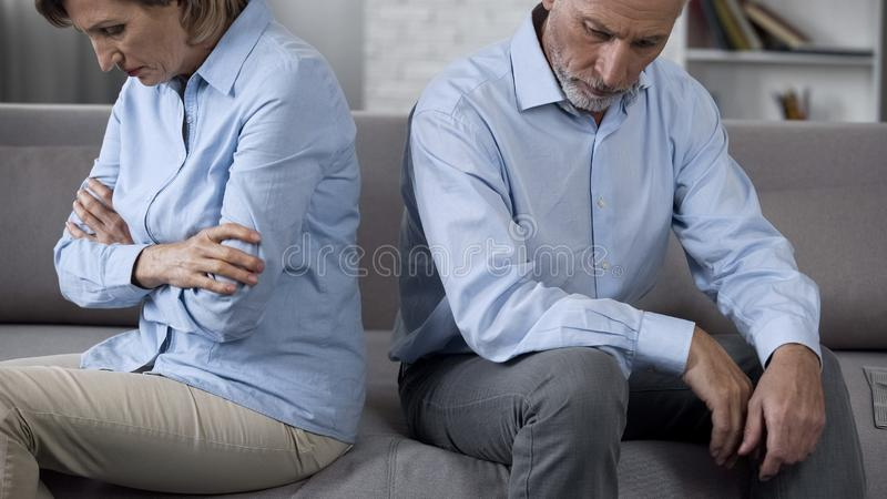 Senior couple sitting on couch overwhelmed with bad news, feeling depressed royalty free stock images