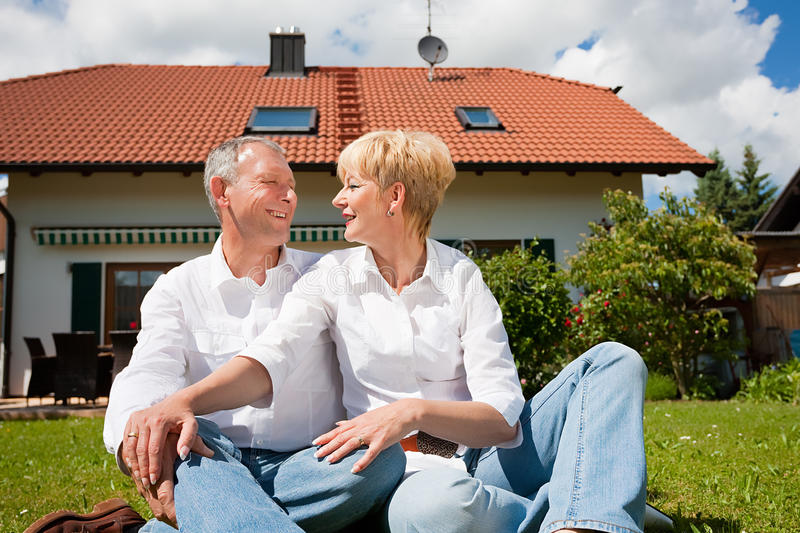 Senior couple sitting in front of their home stock photography