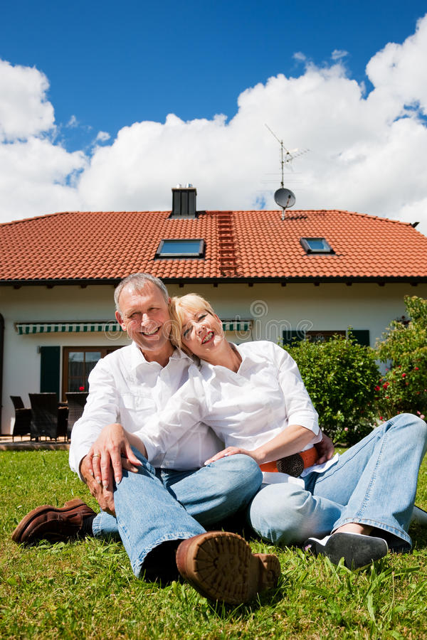 Senior couple sitting in front of their home stock photos
