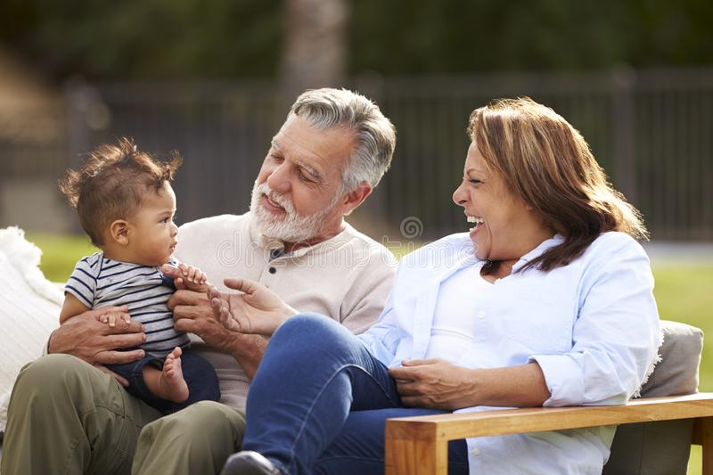Senior couple sitting in the garden with their baby grandson, smiling at him, front view royalty free stock photography