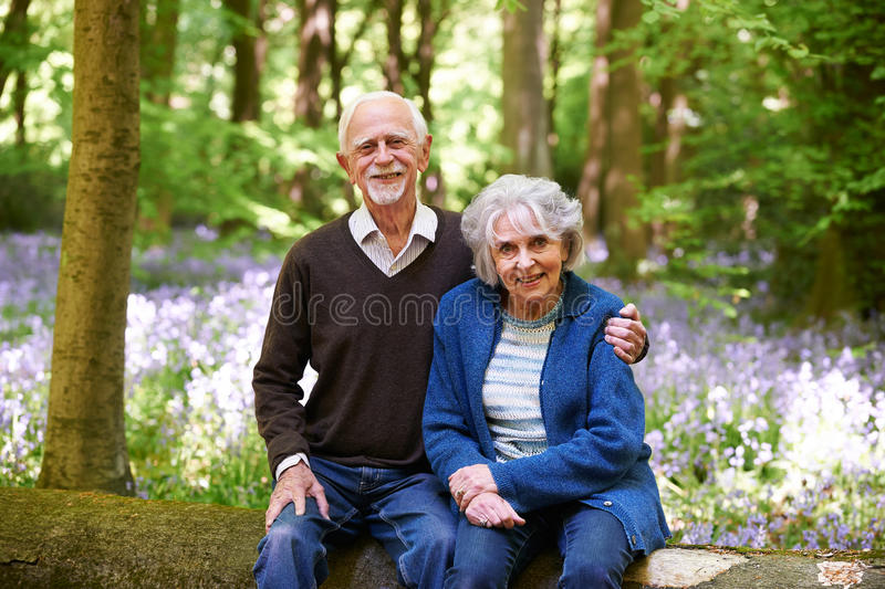 Senior Couple Sitting On Log In Bluebell Woods. Senior Couple Sit On Log In Bluebell Woods stock photos