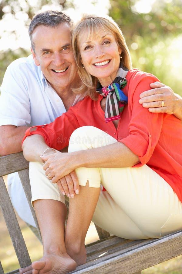 Senior Couple Sitting Outdoors On Bench