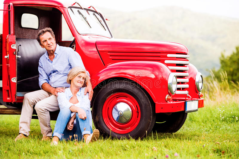 Senior couple sitting at the red vintage car royalty free stock image