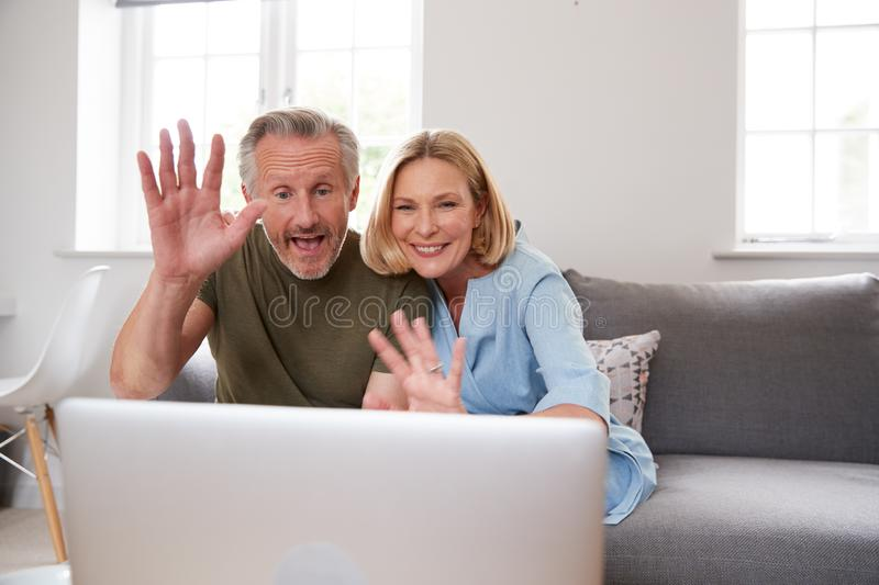 Senior Couple Sitting On Sofa At Home Making Video Call Using Laptop Computer Together royalty free stock photos