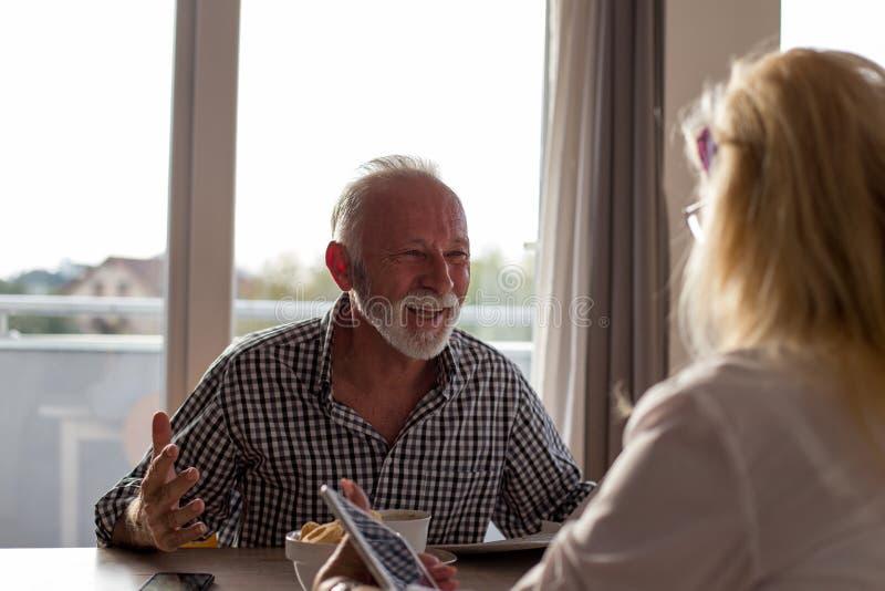 Senior couple talking at table royalty free stock photos