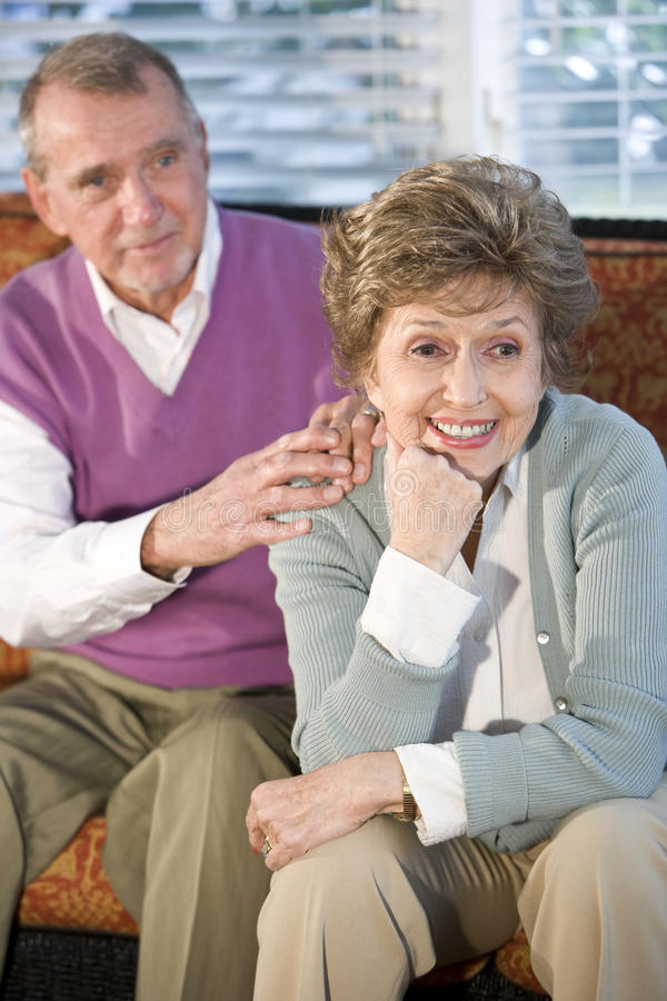 Senior couple sitting together, focus on woman. Happy senior couple sitting together on sofa, focus on woman royalty free stock photos