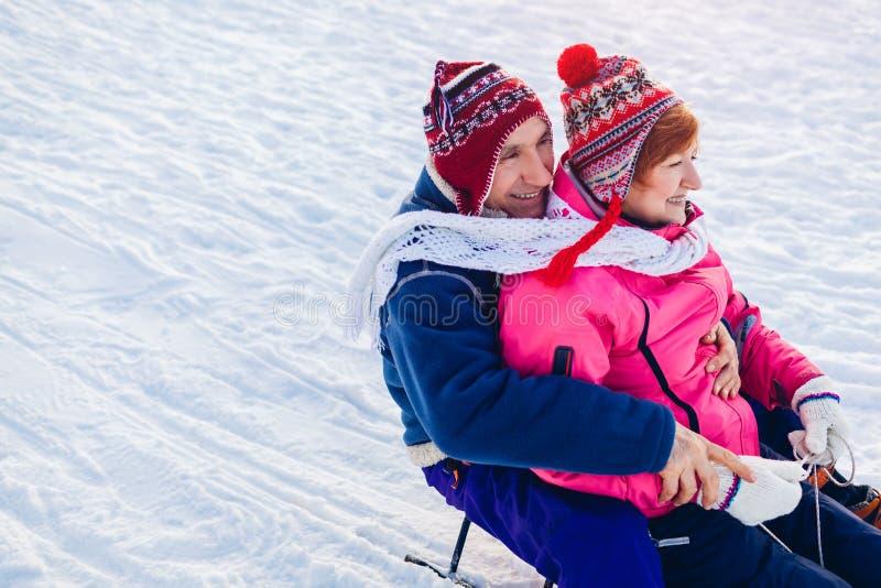 Senior couple sledding down. Family having fun in winter park. Valentine`s day royalty free stock photos