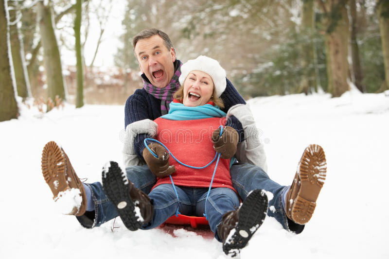 Senior Couple Sledging Through Snowy Woodland Stock Images