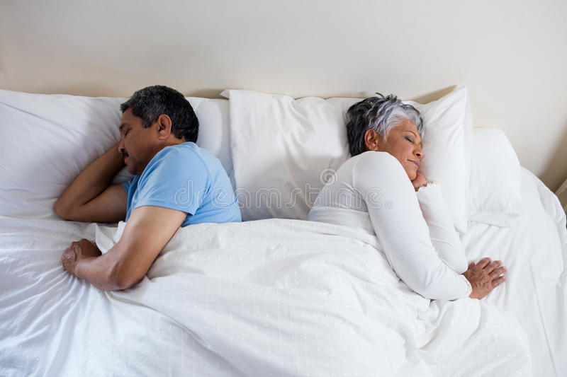 Senior couple sleeping together on bed in bedroom stock photos