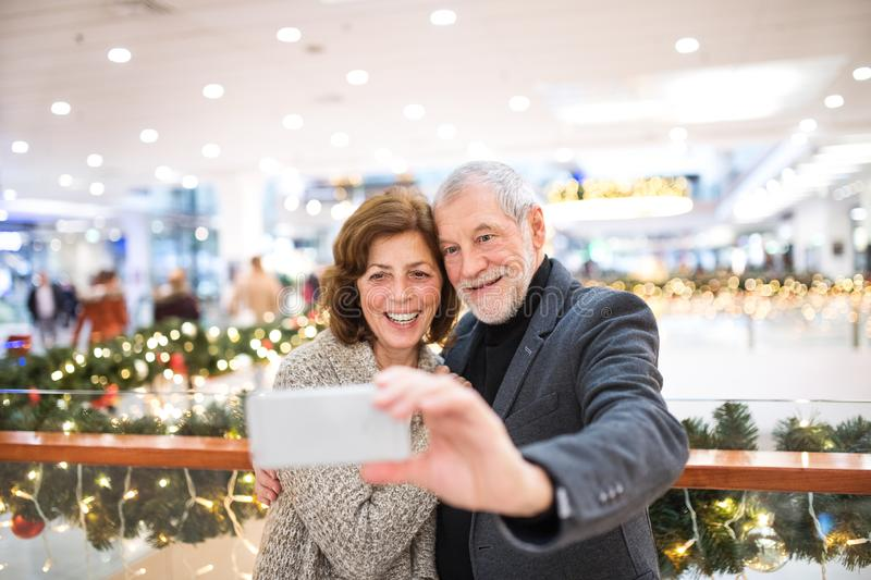 Senior couple with smartphone taking selfie in shopping center at Christmas time. royalty free stock photography