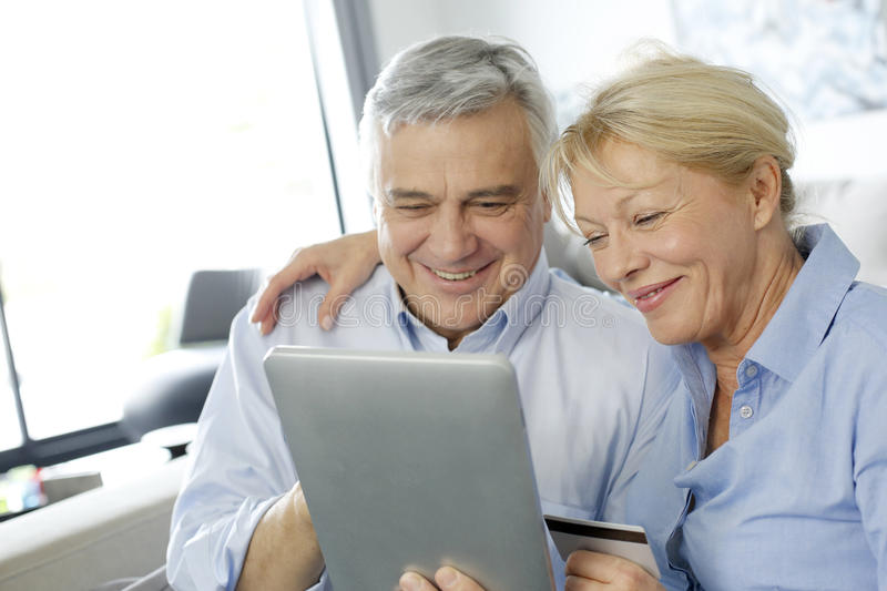 Senior couple smiling using tablet stock image