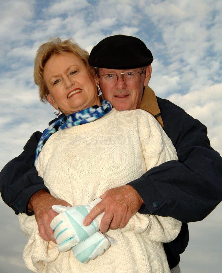 Senior couple snuggling stock photos