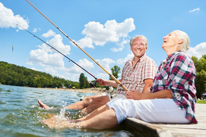 Senior couple splashing with their feet in the water. While fishing on the lake in summer royalty free stock photos