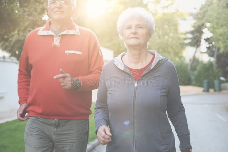 Senior couple in sports clothing having exercise in city stock image