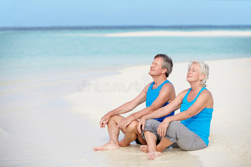 Senior Couple In Sports Clothing Relaxing On Beautiful Beach stock images
