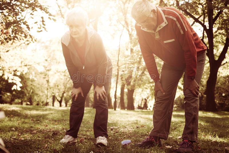 Senior couple in sports clothing resting after exercise. stock image