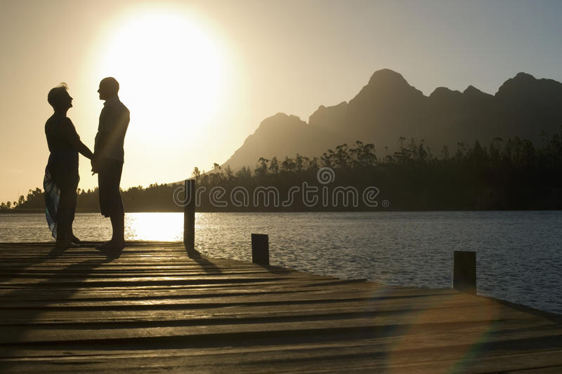 Senior Couple Standing On Edge Of Pier stock photography