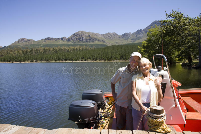 Senior couple standing in motorboat beside lake jetty, woman tying rope to mooring post, smiling, portrait. Senior couple standing in motorboat beside lake jetty stock photo