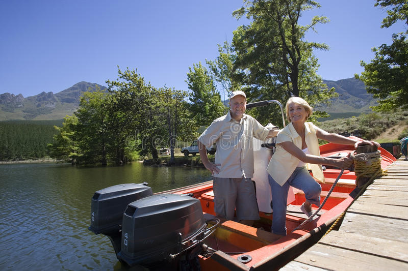 Senior couple standing in motorboat beside lake jetty, woman tying rope to mooring post, smiling, portrait. Senior couple standing in motorboat beside lake jetty royalty free stock photos