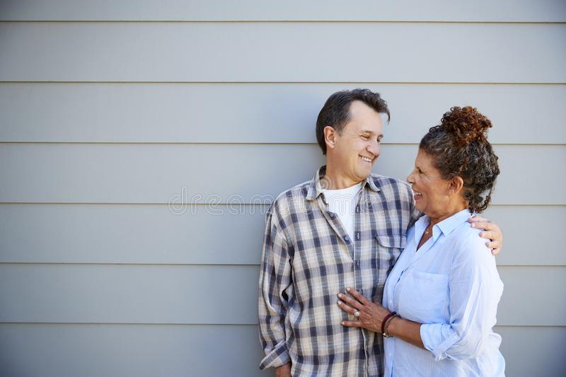 Senior Couple Standing Outside Grey Clapboard House stock images