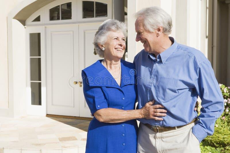 Senior Couple Standing Outside House Stock Photo