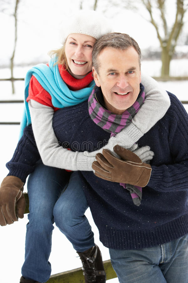 Senior Couple Standing Outside In Snowy Landscape royalty free stock image
