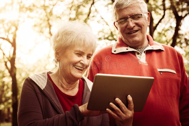 Senior couple standing in park and using iPod. Close up royalty free stock image