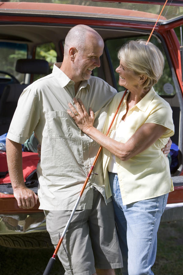 Senior couple standing beside parked SUV, arms around each other, man with fishing rod, smiling. Senior couple standing beside parked SUV, arms around each other stock photo