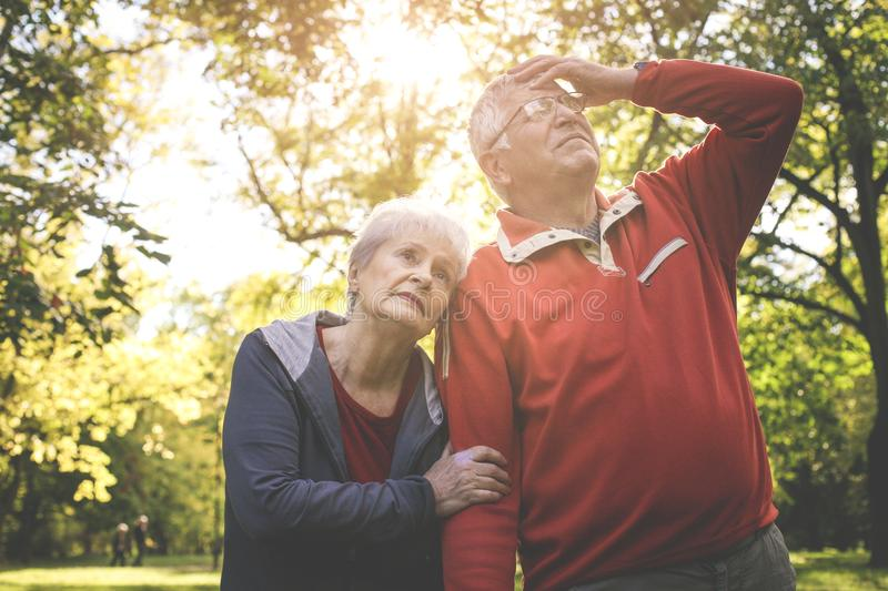 Senior couple standing tired in park after exercise. stock photography
