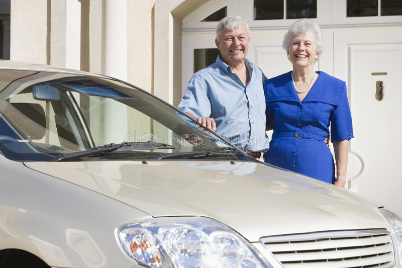 Senior couple standing to new car royalty free stock image