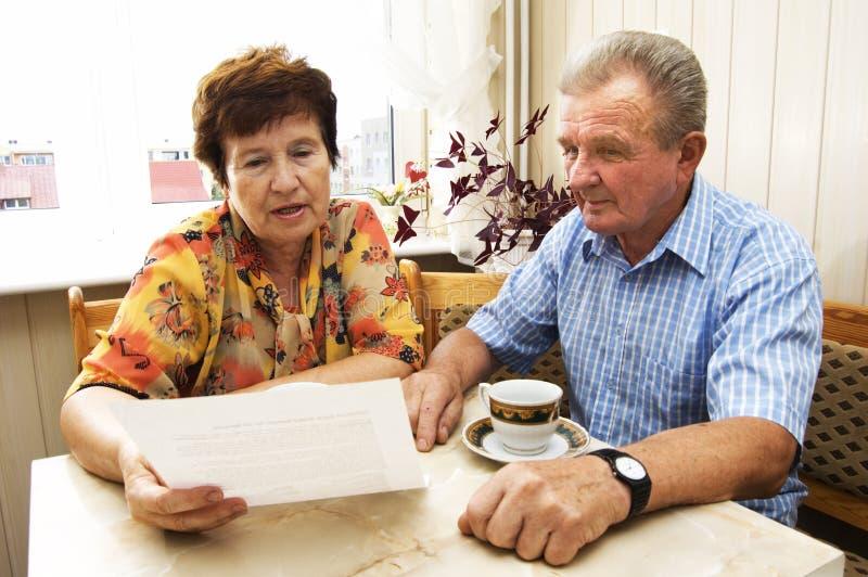 Senior couple studying document royalty free stock photography