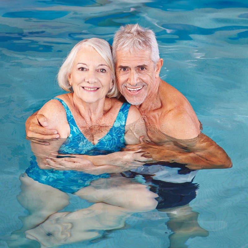 Senior couple swimming in pool stock photos
