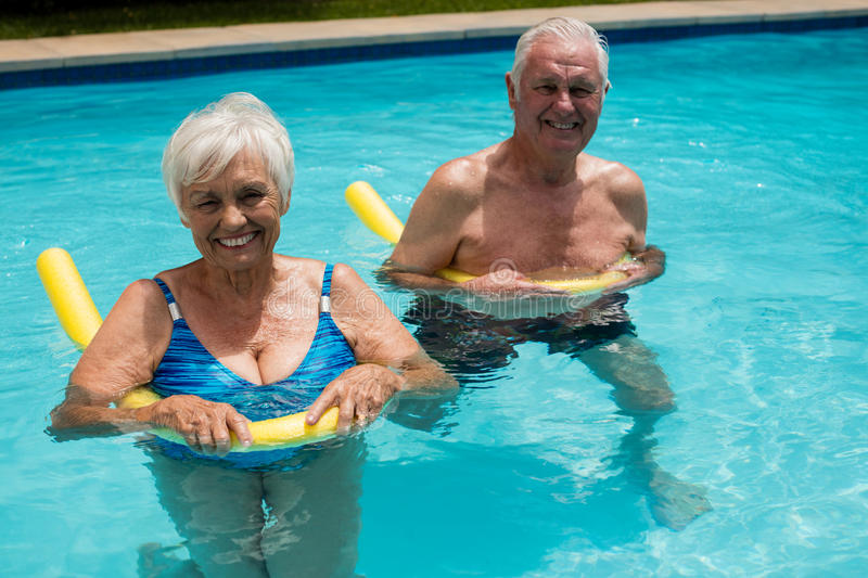 Senior couple swimming in the pool with inflatable tubes royalty free stock images