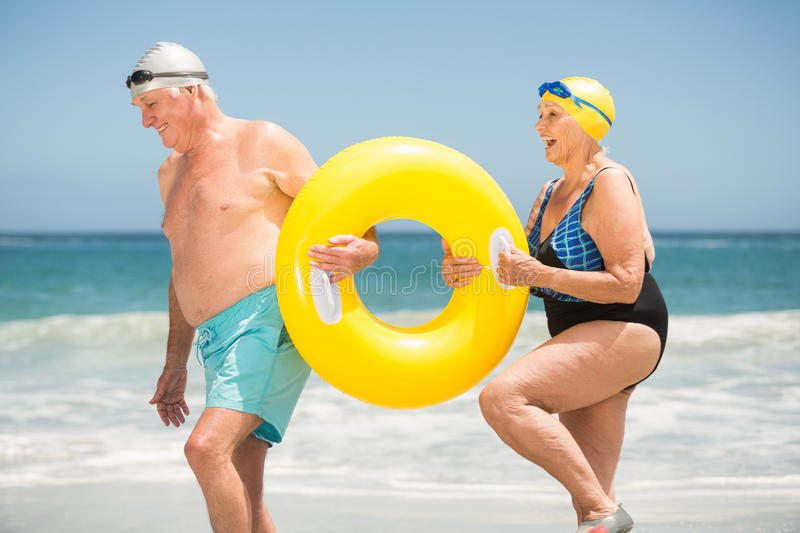 Senior couple with swimming ring at the beach stock images