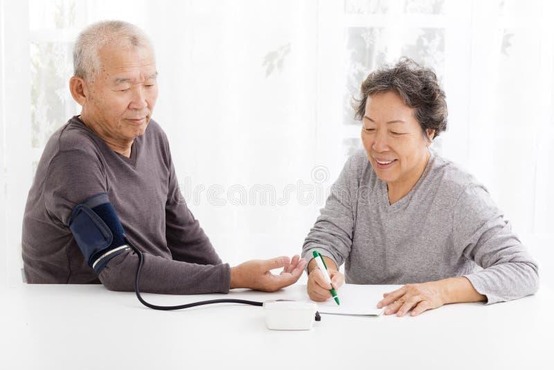Senior couple taking blood pressure in living room. Happy Senior couple taking blood pressure in living room royalty free stock image