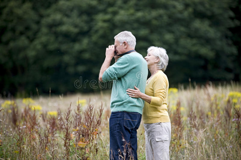 A senior couple taking photographs in a field stock photo