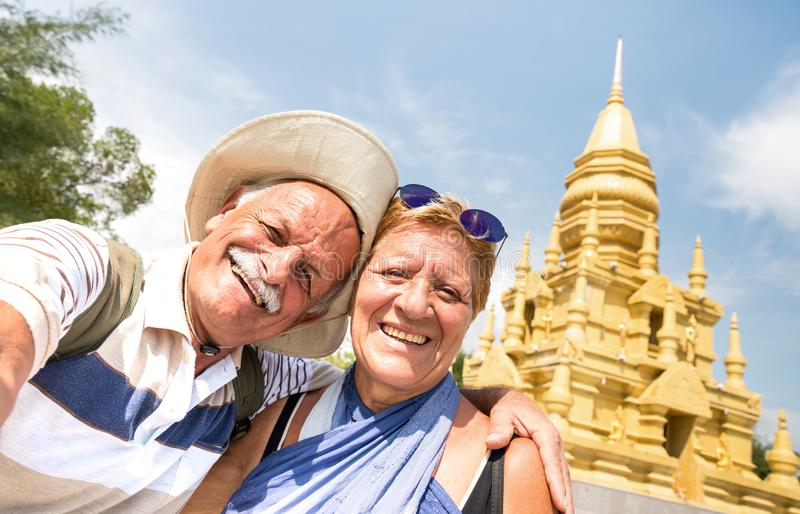 Senior couple taking selfie at golden temple in Ko Samui - Happy retired people traveling to Thailand wonders - Active elderly stock photography