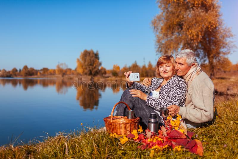 Senior couple taking selfie while having picnic by autumn lake. Happy man and woman enjoying nature and hugging stock photo