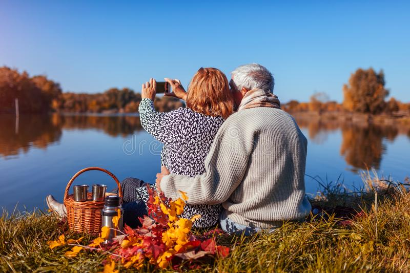 Senior couple taking selfie while having picnic by autumn lake. Happy man and woman enjoying nature and hugging stock images
