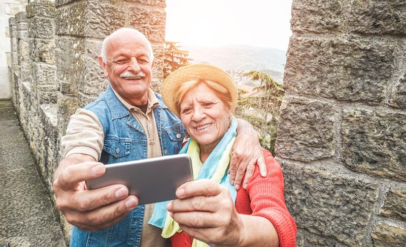 Senior couple taking a selfie inside castle on tour vacation - Mature husband and wife having fun with technology trends - Love,. Relationship and joyful stock photos