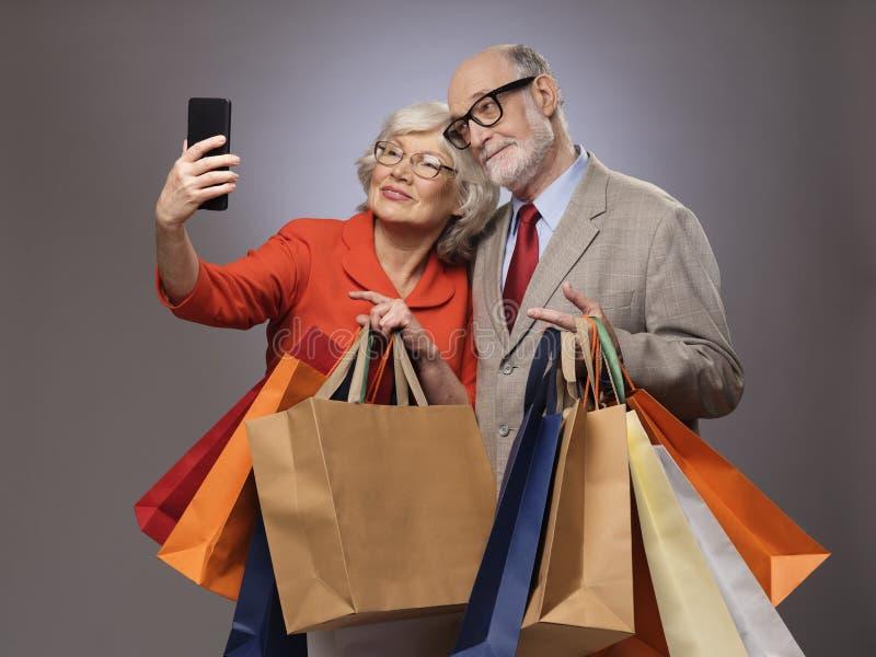 Senior couple taking selfie after shopping stock photos