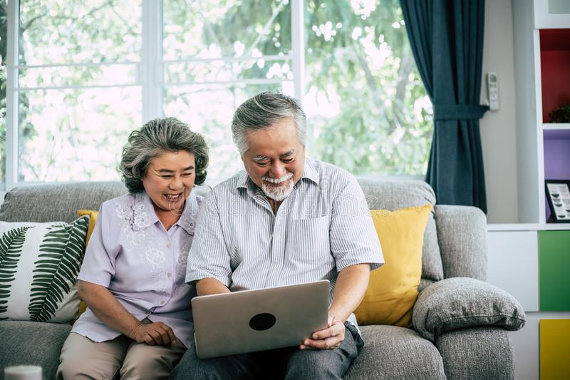 Senior couple talking with laptop computer. At stock photos