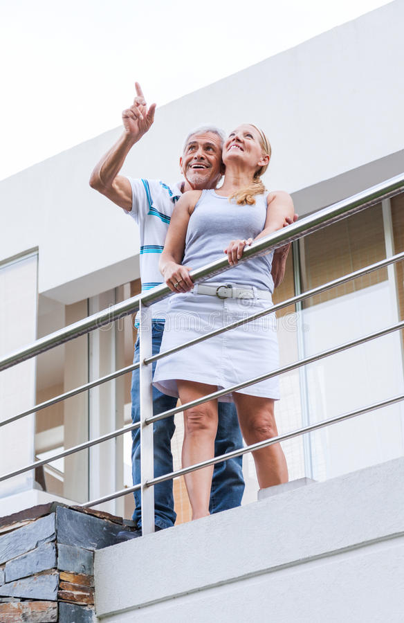 Senior couple terrace balcony modern house. Senior couple terrace balcony of modern house royalty free stock photography