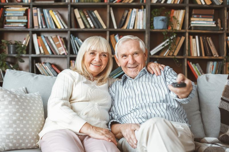 Senior couple together at home retirement concept watching tv holding remote controller. Aged men and women together at home in the living room sitting watching royalty free stock image