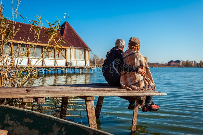 Senior couple of tourists relaxing by autumn lake. Happy man and woman enjoying nature and hugging sitting on pier royalty free stock photo
